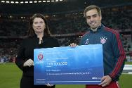 Allianz Arena, Munich, 11 March 2014. Philipp Lahm and Charlotte Lindsey-Curtet, ICRC's director of communication, pose holding the donated cheque of 100,000 euros.