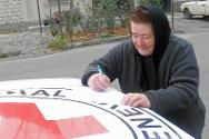 A woman writes a Red Cross message to a relative on the other side of an administrative boundary line.