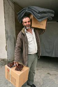 Tripoli. A displaced resident in Kobbeh carrying the items he received from the ICRC.