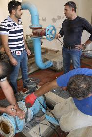 An ICRC engineer and other staff conduct repairs at Loussi water station, in Sultan Yaacoub.