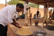 An ICRC delegate works alongside the prisoners to pound corn.