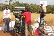 Nigerian Red Cross personnel help a displaced woman balance her load of bedding collected during an ICRC/Nigerian Red Cross distribution operation for some 6,000 people who had taken refuge in Jama'a and Kaura Local Government Areas.