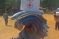 A displaced woman leaves an ICRC/Nigerian Red Cross distribution point with bedding and other essential supplies.