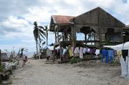Barangay San Fernando, Basey. A child plays in front of a ruined house on the coast.