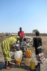 A South Sudan Red Cross volunteer helps a young girl at a water point for civilians displaced by violence in Bentiu.