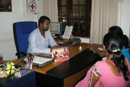 A family visits an ICRC office to receive financial assistance so they can visit a detained relative.
