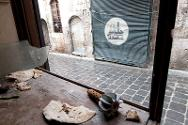 Old city, Aleppo, Part of a mortar bomb lies in the remains of a shop window, its deadly menace contrasting oddly with pieces of life-giving bread.