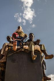 Migrants perch on their truck.