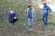 ICRC engineers install a pipe as part of a project to bring mains water to the houses of the village.