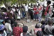 Volunteers from the South Sudan Red Cross explain how to use water purification tablets.