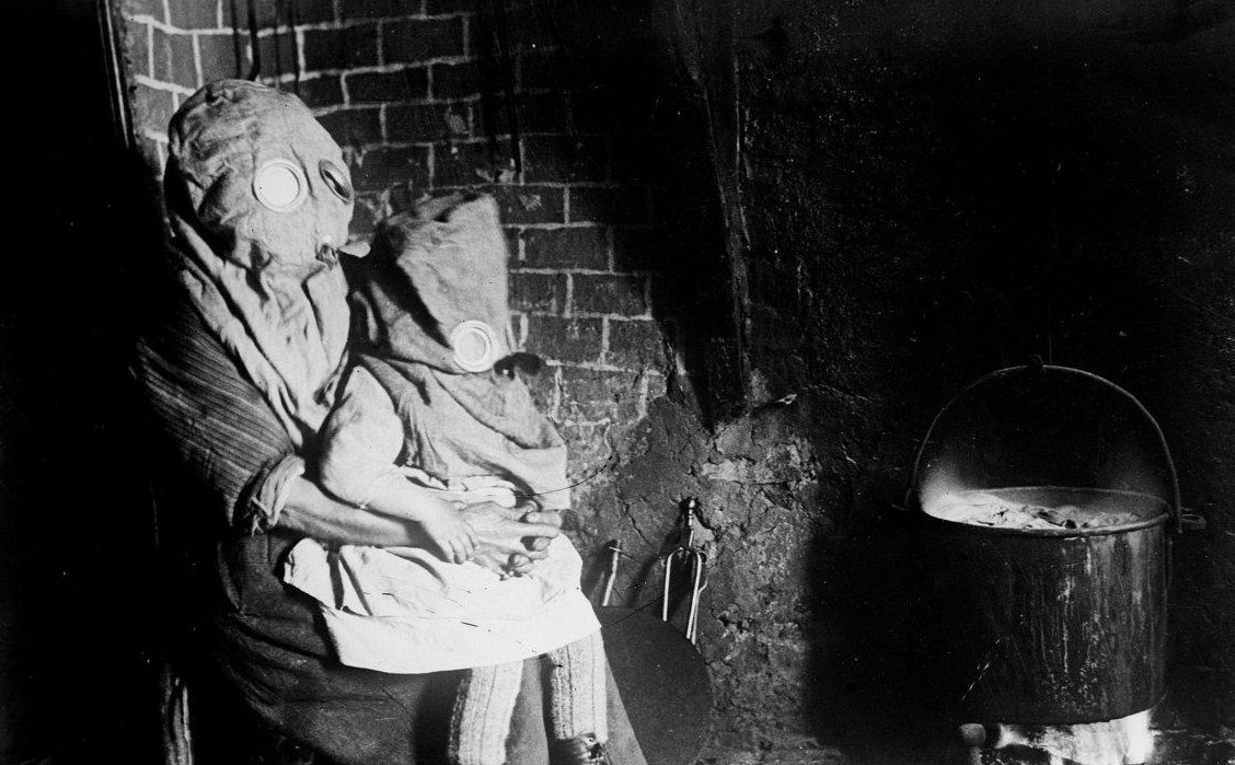 A mother and child wear their gas masks while cooking on an open fire.
