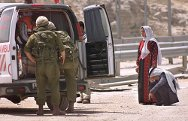 7 May 2002. Israeli soldiers inspect a Palestinian ambulance on its way to Jerusalem at the West Bank army checkpoint of Kalandia.