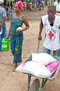 Granpain, Bangolo, Man, Côte d'Ivoire. A volunteer from the Ivorian Red Cross society helps a woman transport food.
