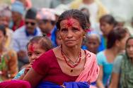 Kohalpur, Banke district, Nepal. The mother of a missing person at a commemoration ceremony, with her grandchild on her back. Families regularly hold events as part of their efforts to find out what happened to missing relatives and to deal with their loss.