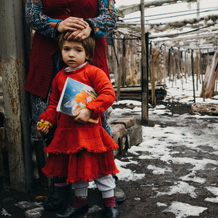 A mother and child stand outside their house damaged by fighting in Semenovka, eastern Ukraine CC BY-NC-ND / ICRC / M. Dondyuk