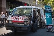 A replica of a burnt-out ambulance at Sydney's peaceful Darling Harbour, peppered with bullet holes and with its doors ripped off by an explosion.