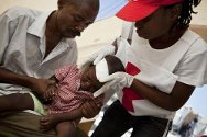 Haiti, Port-au-Prince. Haitian Red Cross volunteers give first aid to a child at a first-aid post set up by the ICRC.