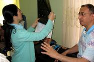 Profesionales que se han capacitado en rehabilitación física examinan a un paciente y observan su placa radiográfica.