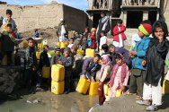 Gazergah, Herat, Afghanistan. Children fill jerrycans at one of the six taps that serve the whole community.