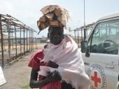 一名南苏丹难民得到了木材和肥皂,这些物资将帮助她照顾自己5个月大的婴儿和其他三个孩子。