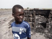 A child stands in front of his burned home in Leer, South Sudan on 23 May 2015. CC BY-NC-ND / ICRC / P. Krzysiek