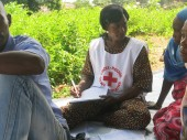 A Red Cross volunteers fills in a tracing request form for this lady.