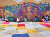 O artista urbano Guache e familiares de desaparecidos, em frente a um mural em homenagem a seres queridos. © CICV/J.S. Uribe