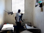 Port-de-Paix civilian prison. An ICRC hygienist supervises a detainee cleaning a cell.