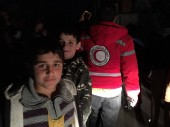 Children wait by a truck as aid is unloaded in the besieged area of Al Houleh.