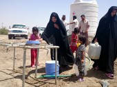 People collecting water from a water-supply point built by the ICRC in Diwaniya. /ICRC/. Baqer