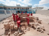 Red-clad Somali prisoners build a brick wall inside the Bossasso prison grounds.