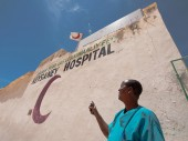 A member of the medical staff at Keysaney Hospital points to the Somalia Red Crescent branding that patients see upon arrival.