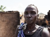 A resident of Leer, South Sudan, stands in front of her mud and straw home shortly after it was burned down.