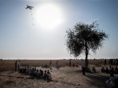 South Sudan. People wait for the ICRC to begin distributing aid as a plane drops food rations in the distance.