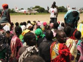 Women of the Leer, South Sudan area sit on the town's dirt airstrip during a food and aid distribution held by the ICRC.