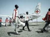 South Sudan Red Cross volunteers and ICRC staff unload fishing kits from a plane for a distribution to take place that day.