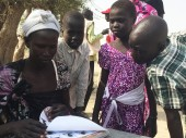 In search of their loved ones, a group of people in Leer review a book containing photos of South Sudanese children.