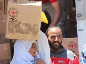 A woman in Mouadamiya  receives an ICRC relief package, delivered by SARC volunteers.