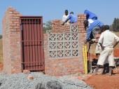 Detainees construct a pump house built to secure the borehole pumps.