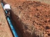 在押人员们铺设管道,连接三个井眼和为奇库鲁比监狱建筑群供水的水库。