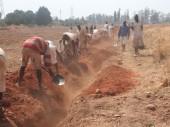 在押人员填埋连接井眼和水库的管道。