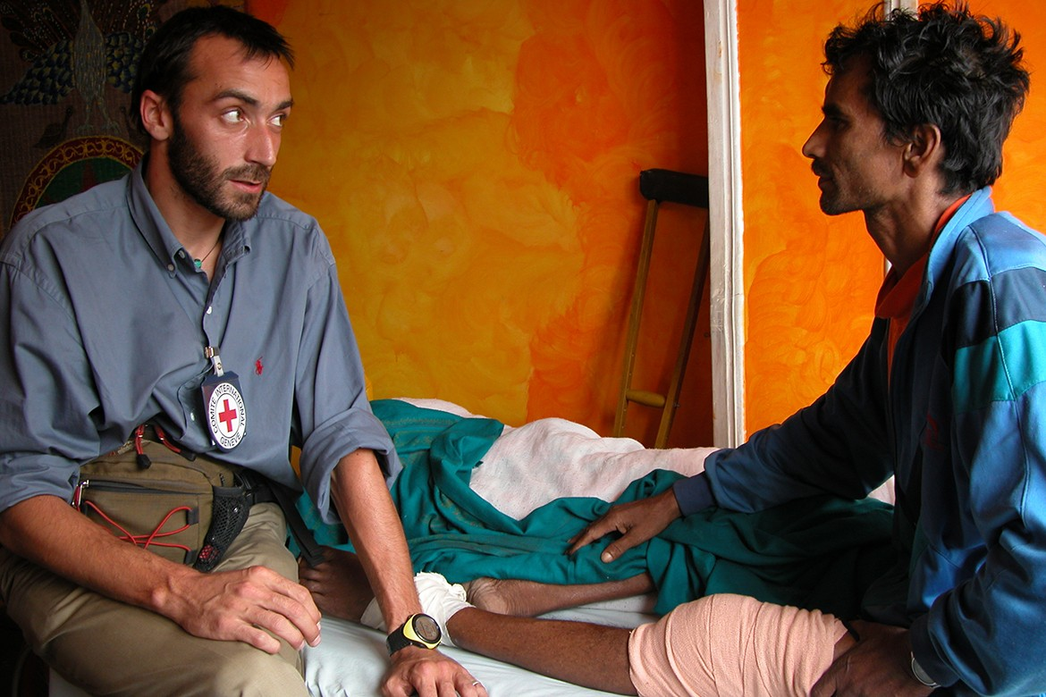 ICRC delegate talking with a war wounded man at a Hospital in Kathmandu, Nepal.