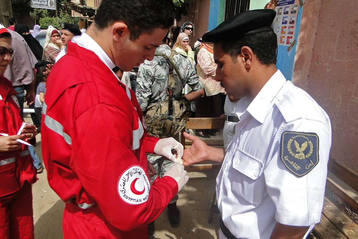 Red Crescent volunteer providing first aid to a wounded policeman in Cairo, Egypt.