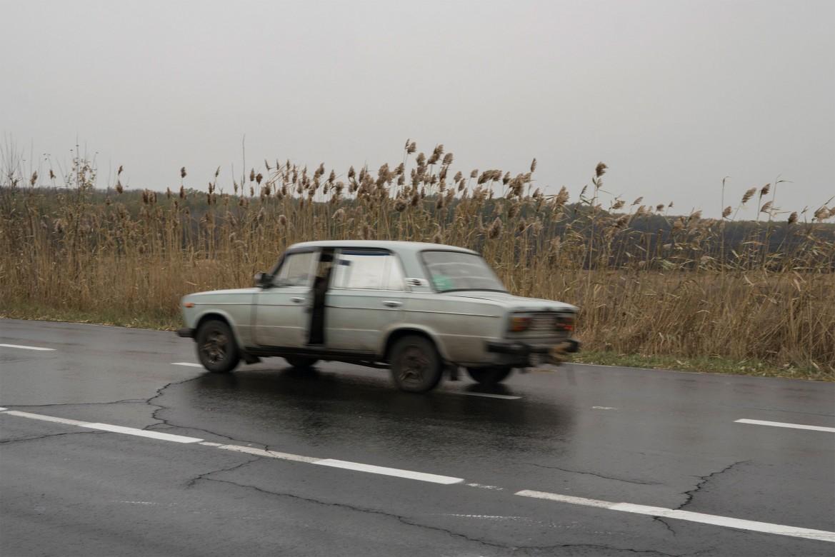 2016年,乌克兰,塞梅尼夫卡(Semenivka)。一辆汽车行驶在前线附近村庄的一条主路上。