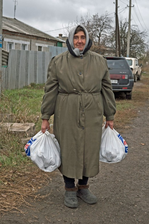 Vodiane, Ukraine, 2016. The woman carrying bread that was provided by the ICRC.