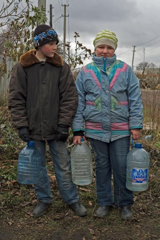 2016年,乌克兰,沃佳内(Vodiane)。村里的孩子们提着水。