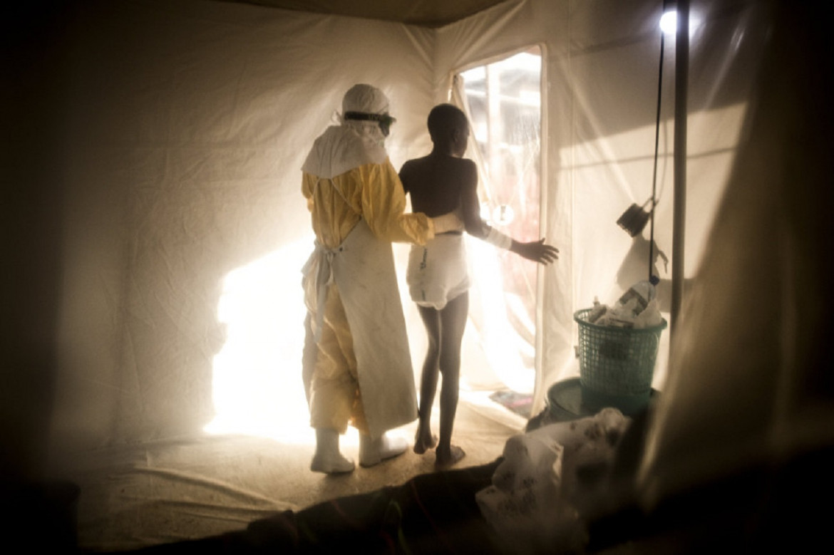 A health worker helps a patient with Ebola out of the isolation ward. Beni, North Kivu province