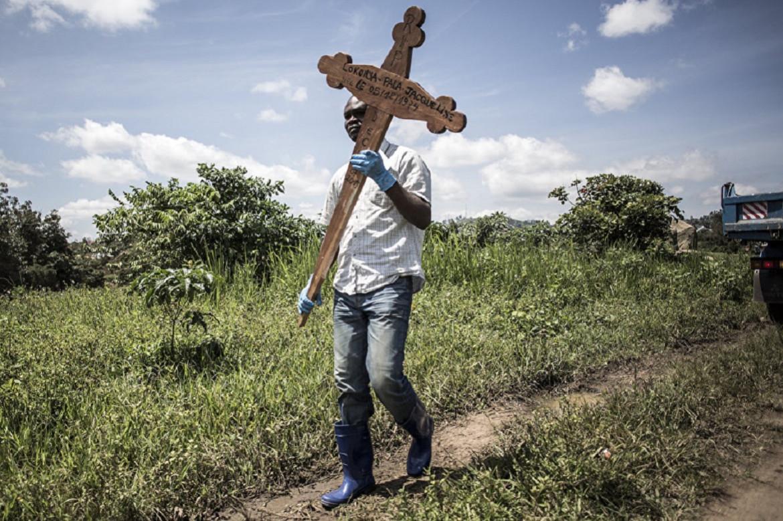 12 juillet 2019, Beni. Un proche d'une victime d'Ebola porte une croix jusqu'à un lieu d'inhumation sûr.