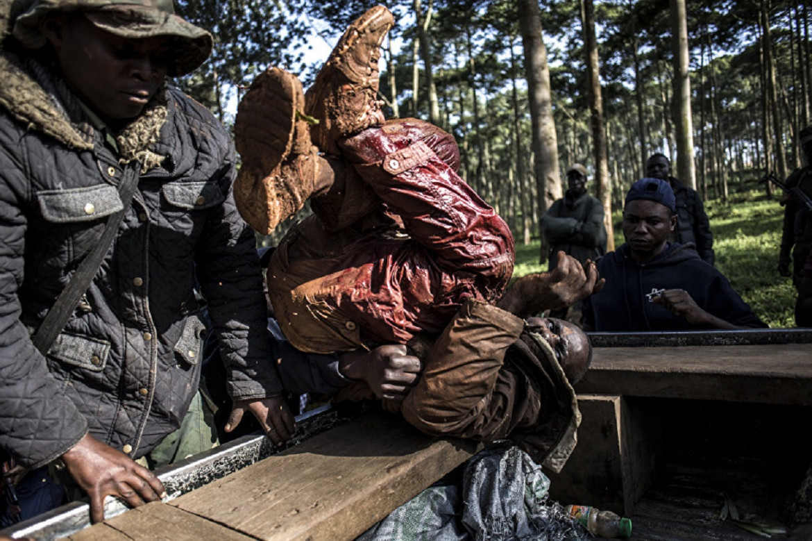 An injured armed group member is thrown into the back of a truck outside a medical center in the city of Butembo, where Ebola is being treated. The city is at the epicenter of a new outbreak in DR Congo. Armed group members attacked the treatment center on the night of March 9, 2019