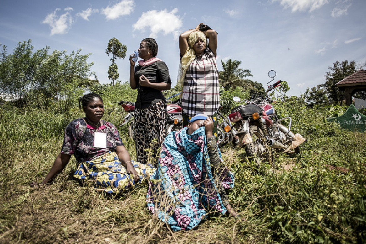 Women mourn the death of a family member during a funeral on the outskirts of Beni, North Kivu province